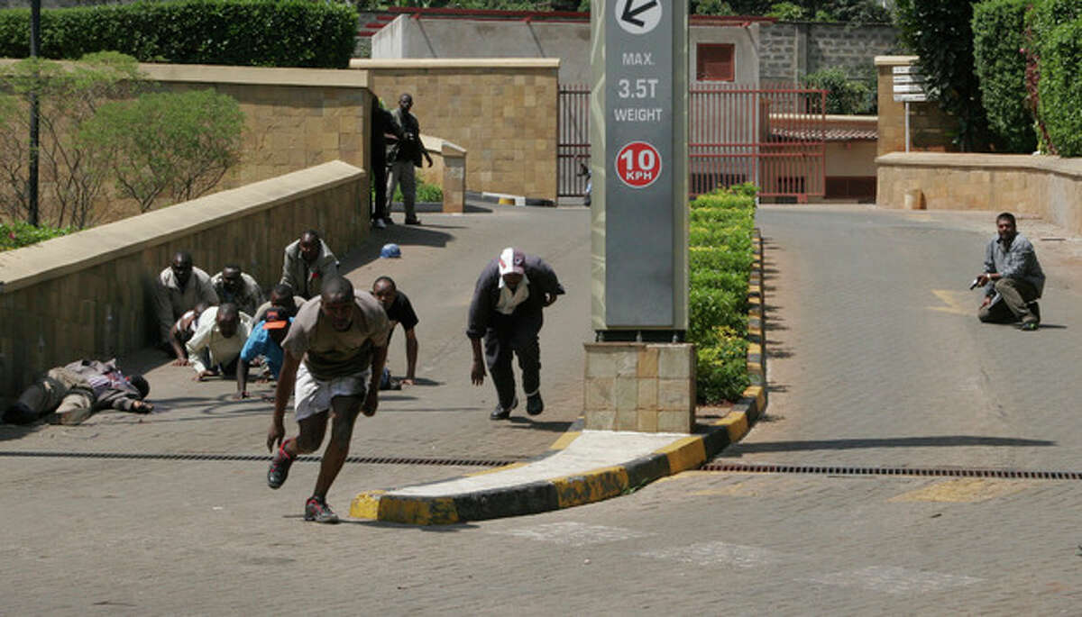 A body, left, lies outside the Westgate Mall, an upscale shopping mall in Nairobi, Kenya Saturday Sept. 21 2013, where shooting erupted when armed men attempted to rob a shop, according to police. Witnesses say a half dozen grenades also went off along with volleys of gunfire in and around the mall. (AP Photo/Sayyid Azim)