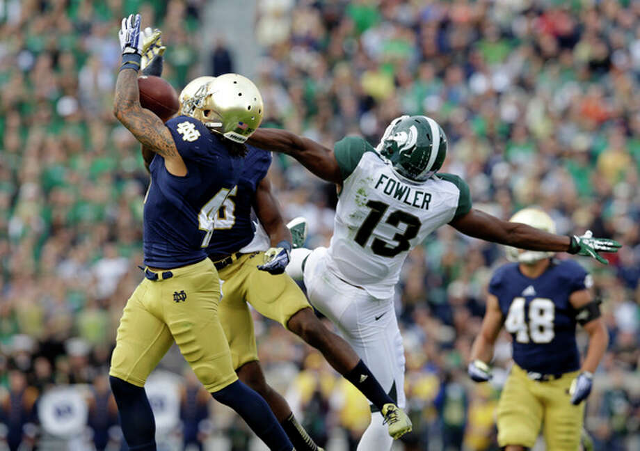 Notre Dame safety Matthias Farley, left, intercepts a pass intended for Michigan State wide receiver Bennie Fowler (13) during the second half of an NCAA college football game in South Bend, Ind., Saturday, Sept. 21, 2013. Notre Dame defeated Michigan State 17-13. (AP Photo/Michael Conroy) / AP