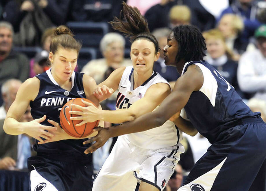 Connecticut's Kelly Faris, center, steals the ball from Penn State's Nikki Greene, right as Greene attempts to pass to Penn State's Maggie Lucas, left, during the first half of an NCAA college basketball game in Storrs, Conn., Thursday, Dec. 6, 2012. (AP Photo/Jessica Hill) / FR125654 AP