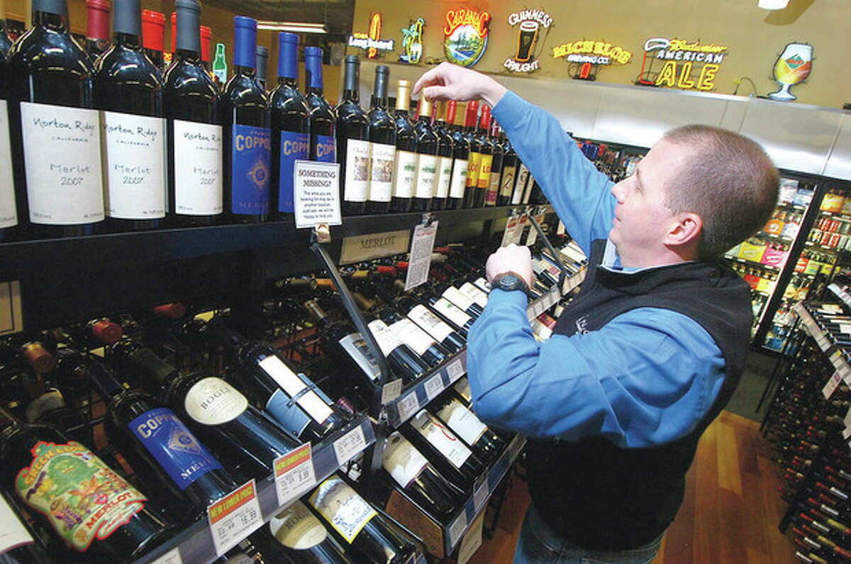 Owner Mitch Ancona straightens a display of fine wines at Ancona's Wines and Liquors in Ridgefield.
