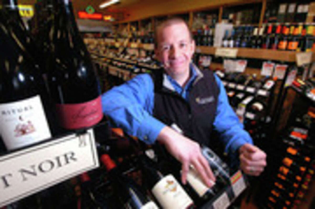 Mitch Ancona, owner of Ancona's Wines and Liquors, stands near the Pinot Noir's in his Ridgefield Store.