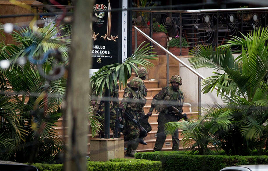 Soldiers from the Kenya Defense Forces carry a wounded colleague, following the sound of explosions and gunfire, out of the Westgate Mall in Nairobi, Kenya Sunday, Sept. 22, 2013. Associated Press journalists at the scene of a hostage standoff said a barrage of gunfire erupted from the upscale Kenyan mall Sunday morning and moments later two wounded Kenyan security forces were carried out of the mall. (AP Photo/Ben Curtis) / AP