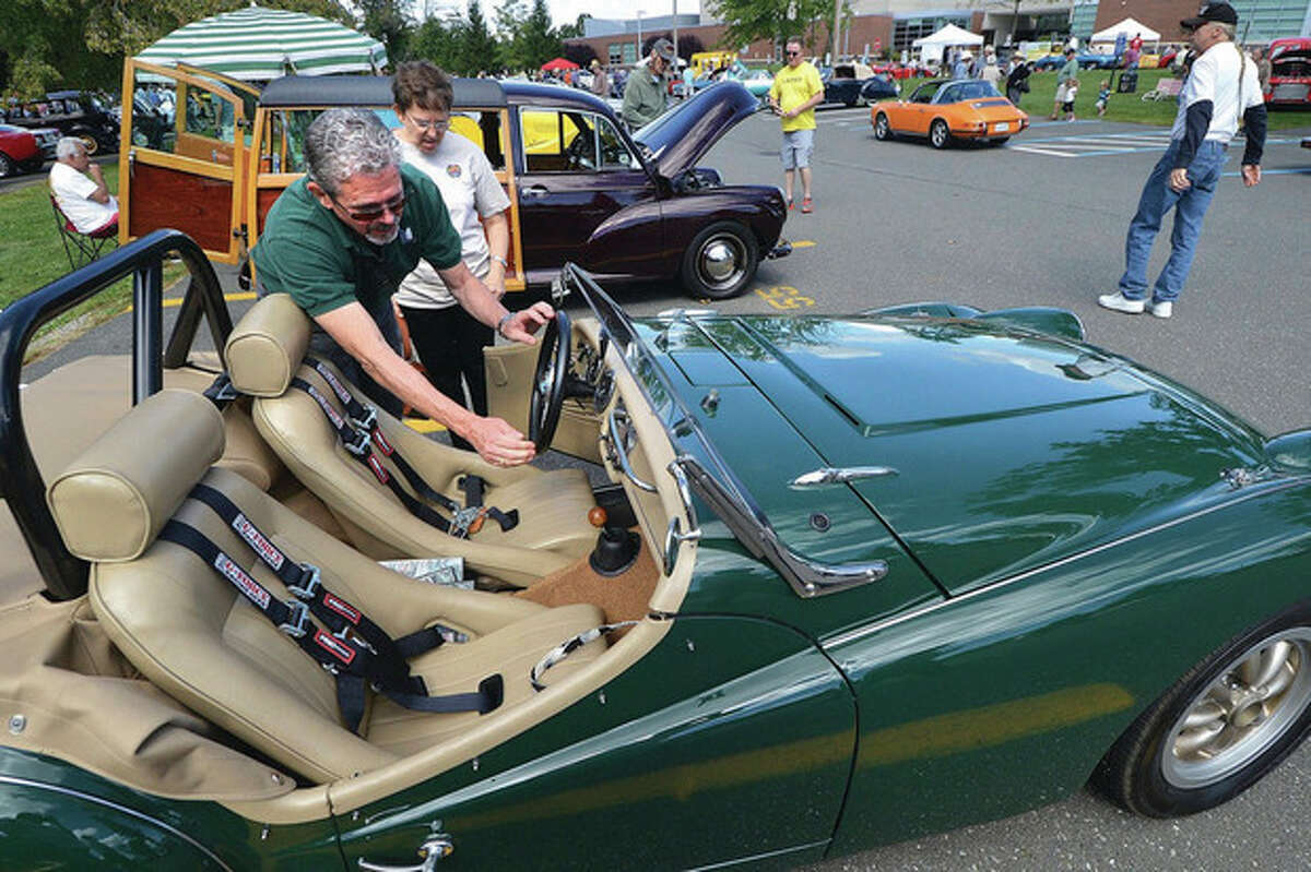 Wilton's Kevin and Moira Craw get ready to start up their 1963 Triumph TR3 at the Alden Sherman Classic Car show in Weston. A 5 plus year project for him to rebuild and customize the car so it is car-show caliber.