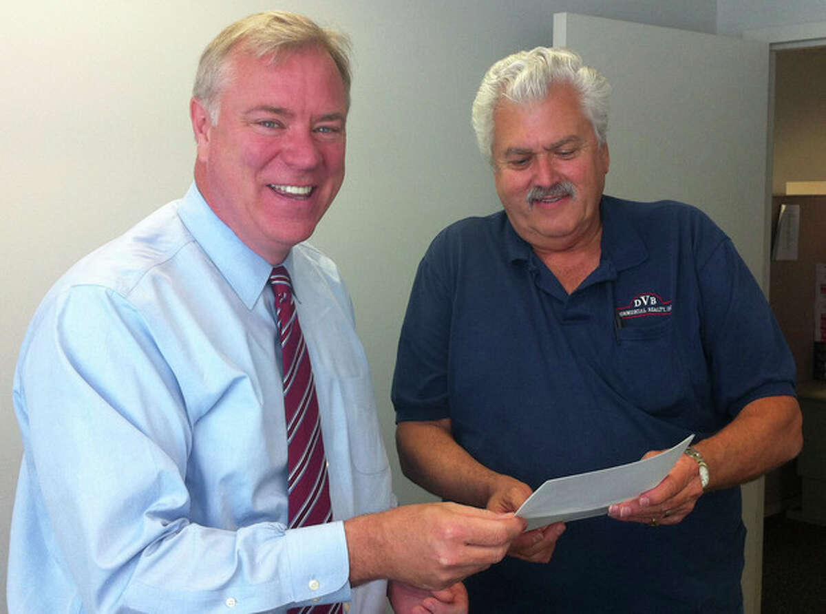 Contributed photo Robert J. Virgulak, Oak Hills Park Authority chairman, right, gives Robert Barron, the city's director of management and budgets, checks totaling $218,000 for money owed the city by the authority.