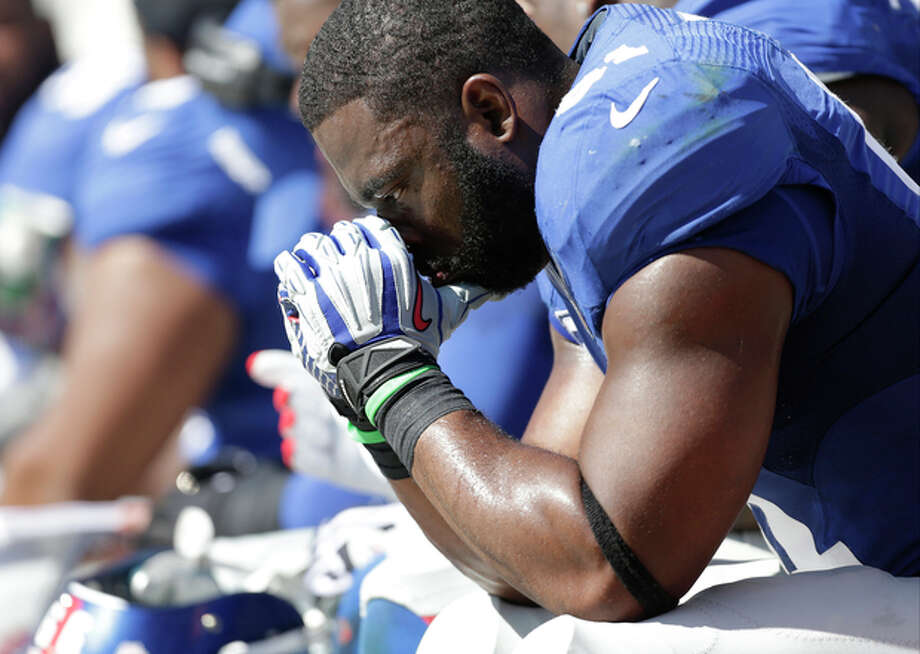 FILE - In this Sunday, Sept. 22, 2013, file photo, New York Giants' Justin Tuck sits on the bench during the second half of an NFL football game against the Carolina Panthers in Charlotte, N.C. Their 0-3 start is their worst since 1996 and the worst of the Tom Coughlin era. Their performance in a 38-0 loss to the Carolina Panthers on Sunday was abysmal. (AP Photo/Bob Leverone, File) / FR170480 AP