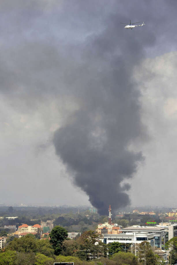 A helicopter flies above as a plume of black smoke billows over the Westgate Mall, following large explosions and heavy gunfire, in Nairobi, Kenya Monday, Sept. 23, 2013. Four large blasts rocked Kenya's Westgate Mall on Monday, sending large plumes of smoke over an upscale suburb as Kenyan military forces sought to rescue an unknown number of hostages held by al-Qaida-linked militants. (AP Photo/Riccardo Gangale)