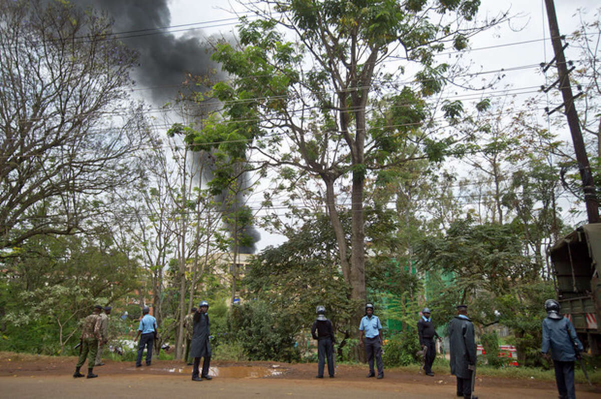 Kenyan police order bystanders and media away from an overlooking hill as a plume of black smoke billows over the Westgate Mall, following large explosions and heavy gunfire, in Nairobi, Kenya Monday, Sept. 23, 2013. Four large blasts rocked Kenya's Westgate Mall on Monday, sending large plumes of smoke over an upscale suburb as Kenyan military forces sought to rescue an unknown number of hostages held by al-Qaida-linked militants. (AP Photo/Ben Curtis)