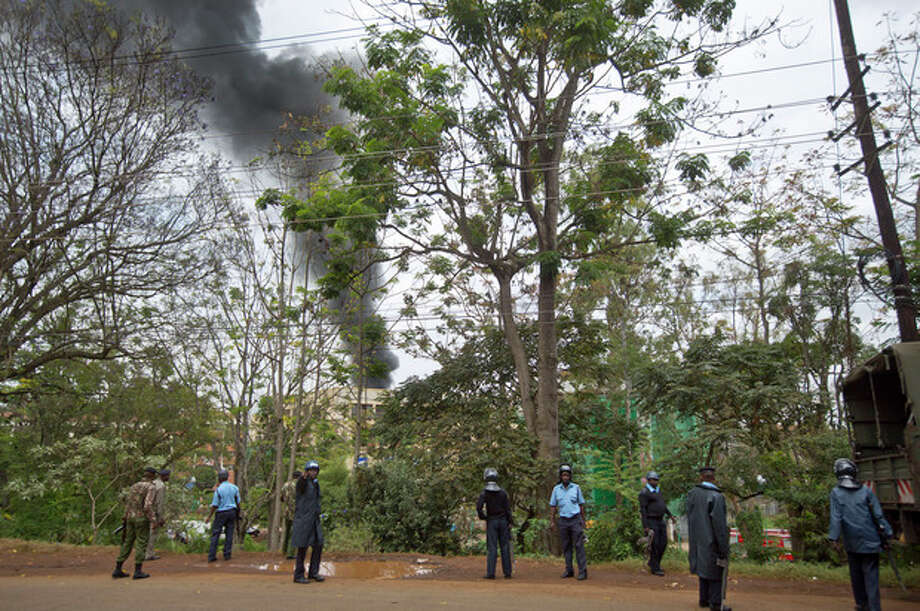Kenyan police order bystanders and media away from an overlooking hill as a plume of black smoke billows over the Westgate Mall, following large explosions and heavy gunfire, in Nairobi, Kenya Monday, Sept. 23, 2013. Four large blasts rocked Kenya's Westgate Mall on Monday, sending large plumes of smoke over an upscale suburb as Kenyan military forces sought to rescue an unknown number of hostages held by al-Qaida-linked militants. (AP Photo/Ben Curtis) / AP