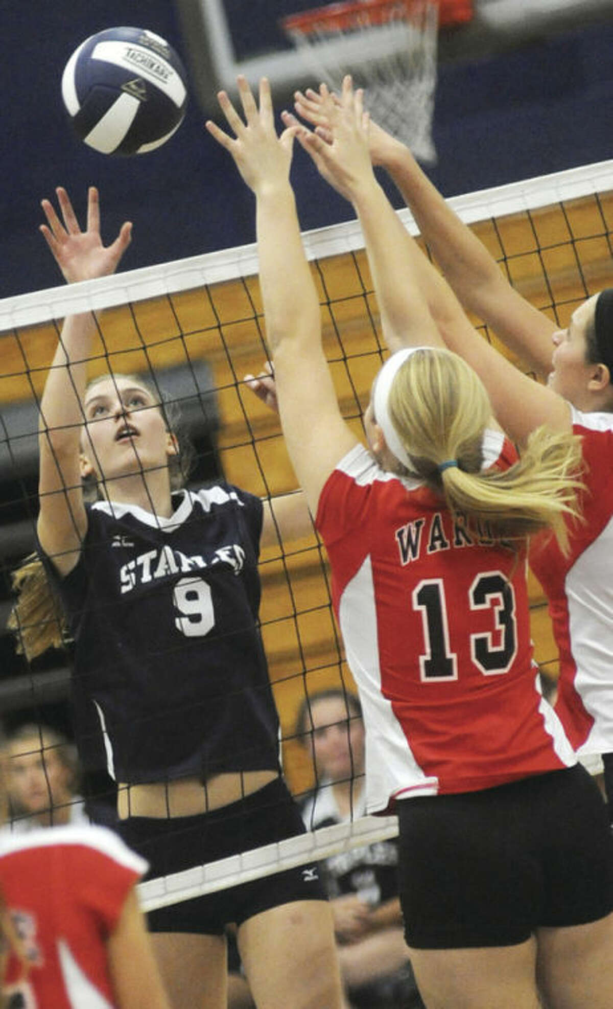 Hour photo/Matthew Vinci Lauren Mushro of Staples, left, andKenxie Burns and Hannah Wolf of Fairfield Warde battle at the net during Monday's FCIAC girls volleyball match in Westport. The Wreckers remained unbeaten with a 3-0 victory.