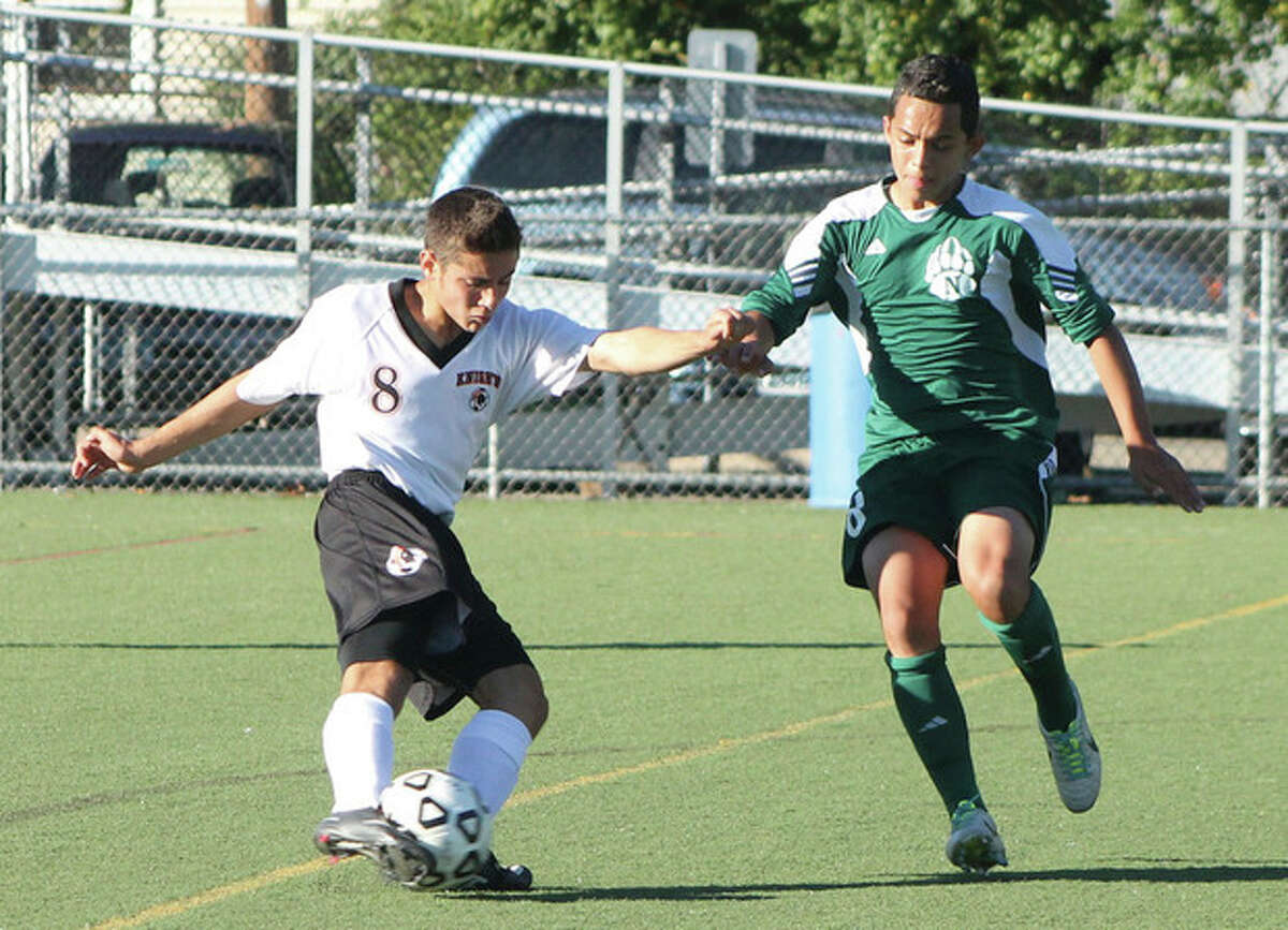 Hour photo/Joe Ryan Stamford's Joe Schinella, left, looks to control the ball as Norwalk's Miguel Argueta moves in during Monday's game in Stamford. The Black Knights won, 3-1.