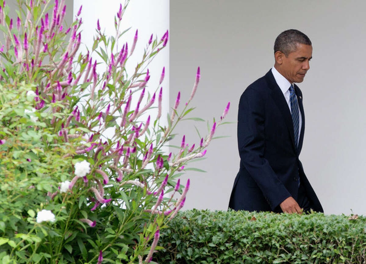 President Barack Obama walks from the Oval Office of the White House in Washington, Monday, Sept. 23, 2013, along to colonnade to join first lady Michelle Obama, as they travel to the United Nations General Assembly in New York. (AP Photo/Carolyn Kaster)
