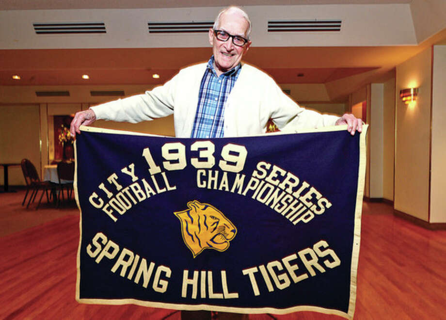 Hour photo/Erik TrautmannMike Errico proudly displays the banner proclaiming the Spring Hill Tigers as the 1939 Norwalk city champions. It was the second of four straight city titles won by the Spring Hill Athletic Association that Errico helped form in 1938. Some 75 years later, the 93-year-old Errico is still involved in the local sports scene. / (C)2013, The Hour Newspapers, all rights reserved