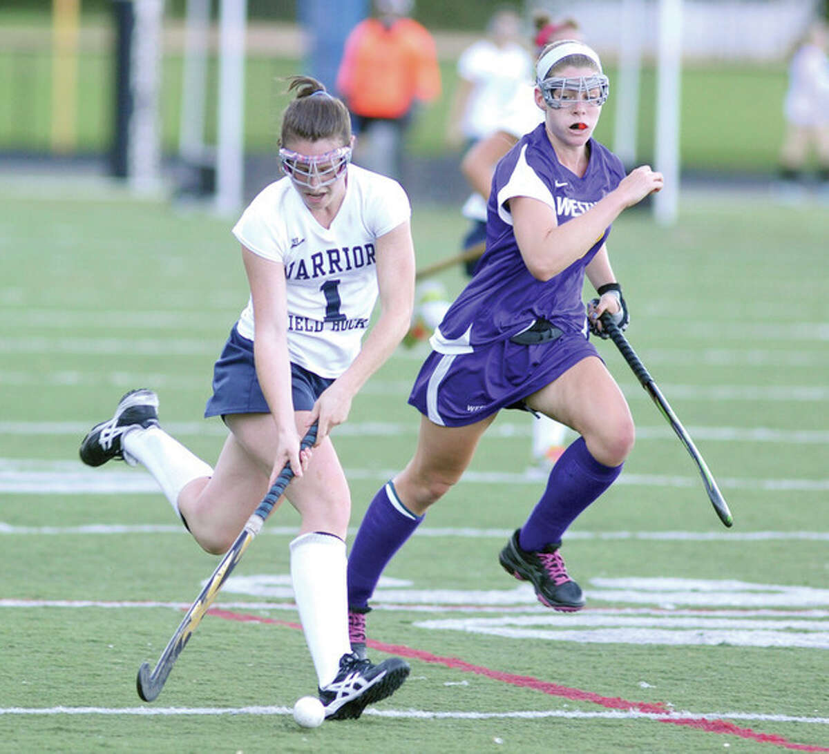 Hour photo/John Nash Wilton's Megan Cunningham, left, races up field as Westhill's Jackie Forde gives chase during Monday's FCIAC game at Fujitani Field in Wilton.