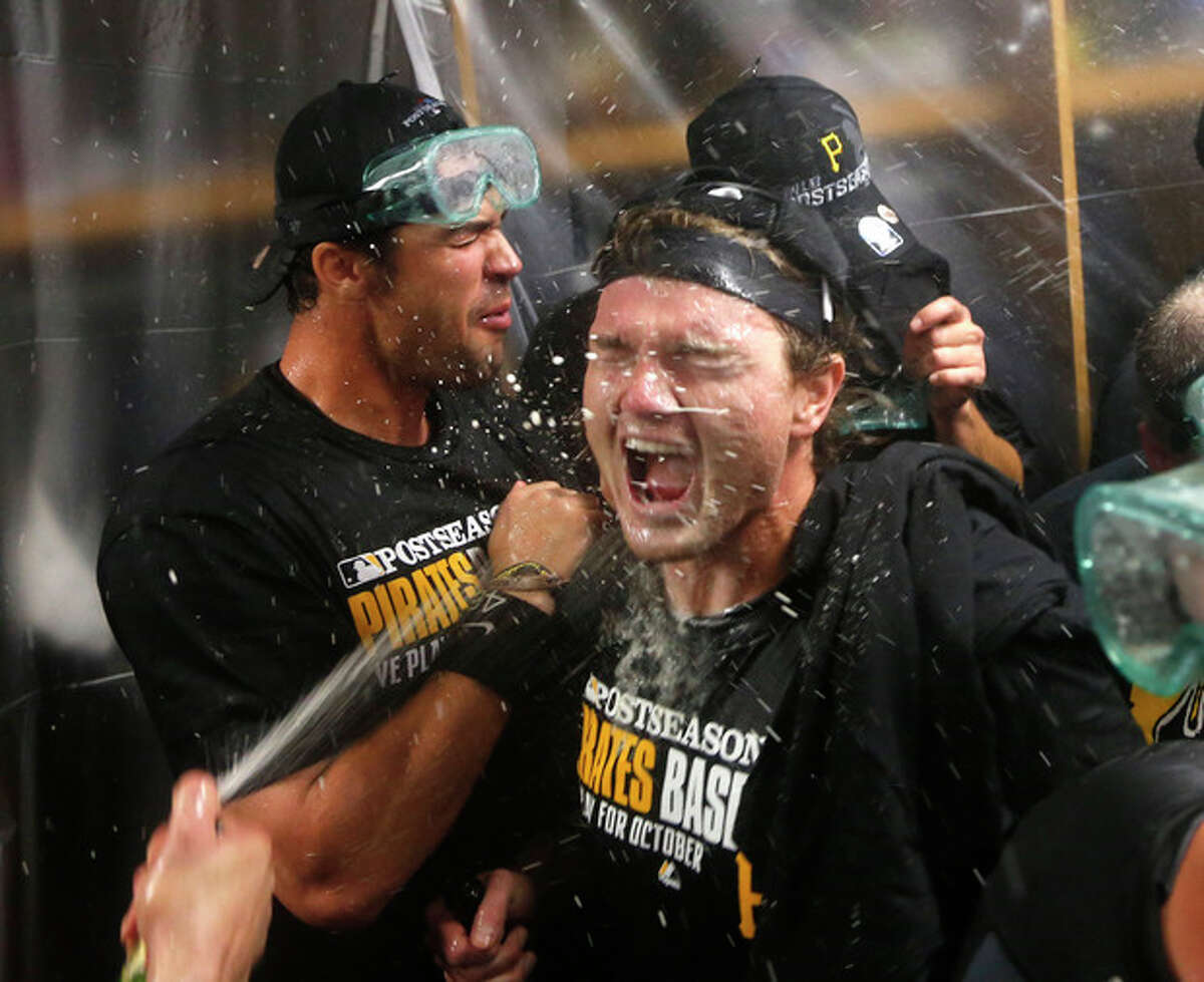 The Pittsburgh Pirates celebrate clinching a post season berth after a baseball game and 2-1 win over the Chicago Cubs Monday, Sept. 23, 2013, in Chicago. (AP Photo/Charles Rex Arbogast)