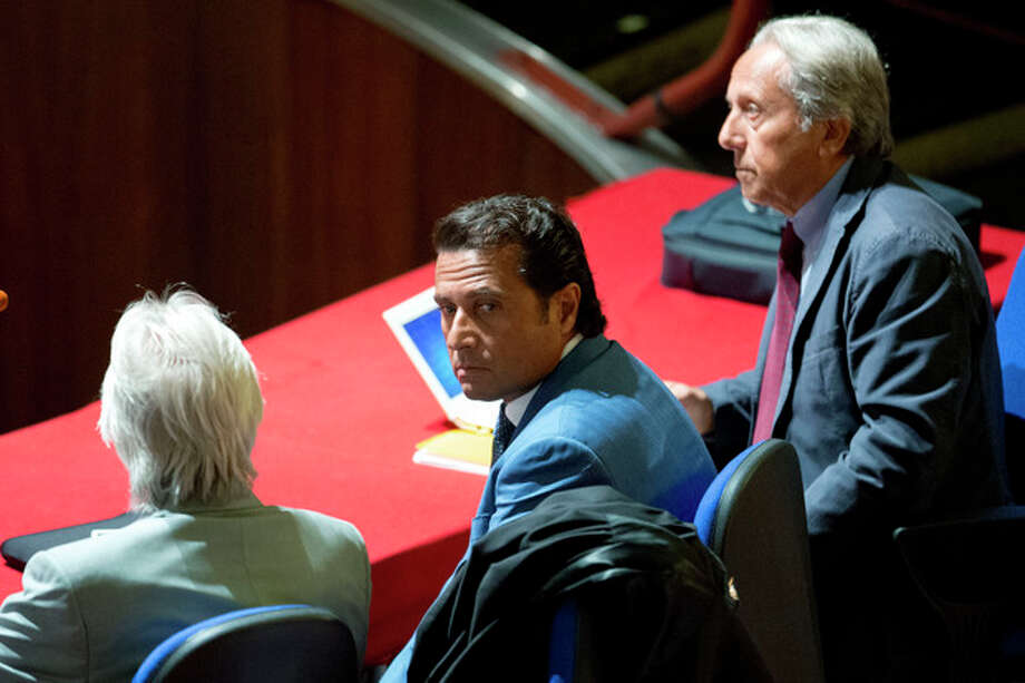 Captain Francesco Schettino, center, sits in the court room of the converted Teatro Moderno theater on the second day of his trial, in Grosseto, Italy, Tuesday, Sept. 24, 2013. The captain of the wrecked Costa Concordia is charged with manslaughter, causing the shipwreck and abandoning ship before the luxury cruise liner's 4,200 passengers and crew could be evacuated on Jan. 13, 2012 when the ship collided with a reef off the Tuscan island of Giglio, killing 32 people. Schettino blames his helmsman for botching a last-minute corrective maneuver that he contends could have prevented the massive cruise ship's collision with the reef. (AP Photo/Andrew Medichini) / AP