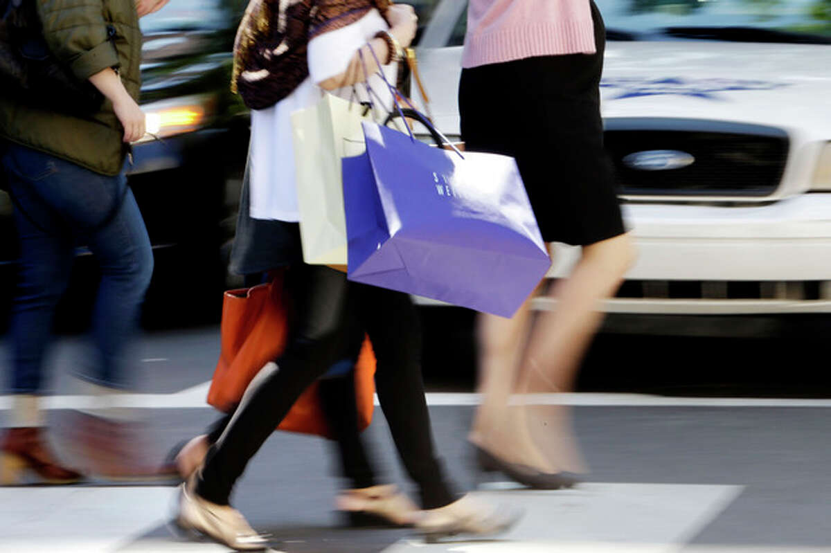 In this Wednesday, Sept. 18, 2013, photo, pedestrians with shopping bags cross a street in Philadelphia. Th e private Conference Board reports on consumer confidence for September on Tuesday, Sept. 24, 2013. (AP Photo/Matt Rourke)