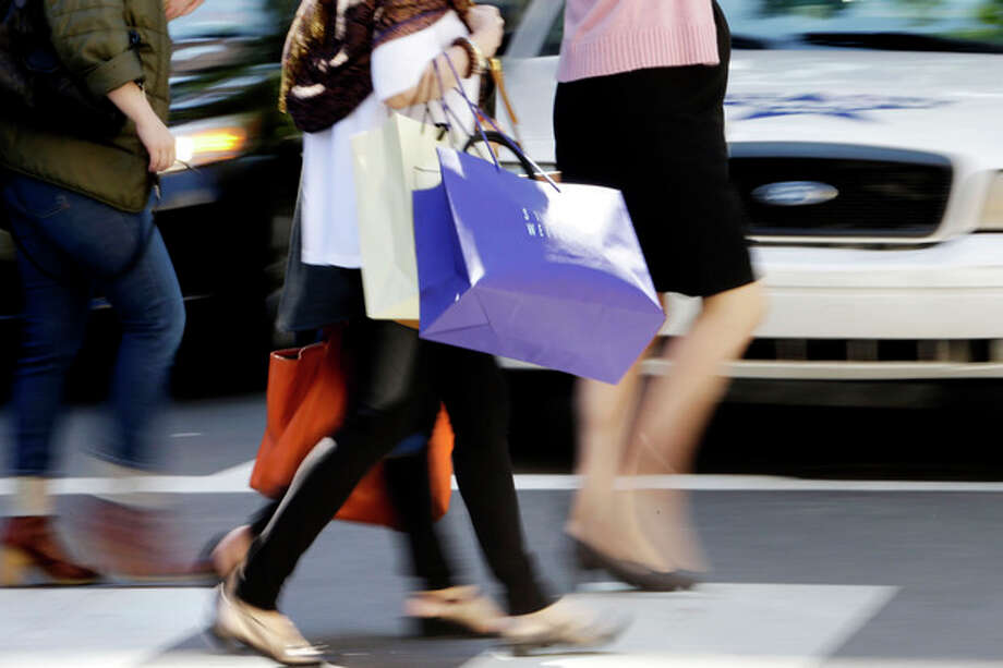 In this Wednesday, Sept. 18, 2013, photo, pedestrians with shopping bags cross a street in Philadelphia. Th e private Conference Board reports on consumer confidence for September on Tuesday, Sept. 24, 2013. (AP Photo/Matt Rourke) / AP