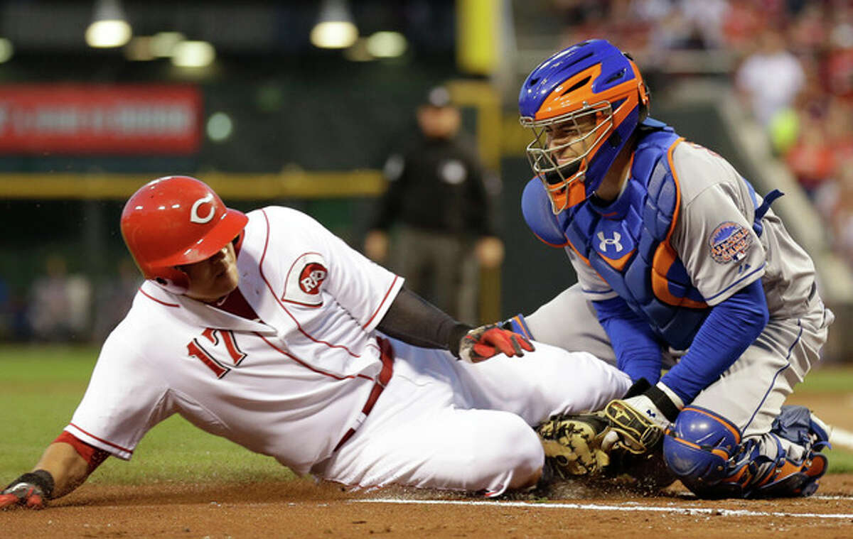 New York Mets catcher Travis d'Arnaud tags out Cincinnati Reds' Shin-Soo Choo (17) at home plate in the first inning of a baseball game, Tuesday, Sept. 24, 2013, in Cincinnati. Choo was trying to score on a hit by Ryan Ludwick. (AP Photo/Al Behrman)