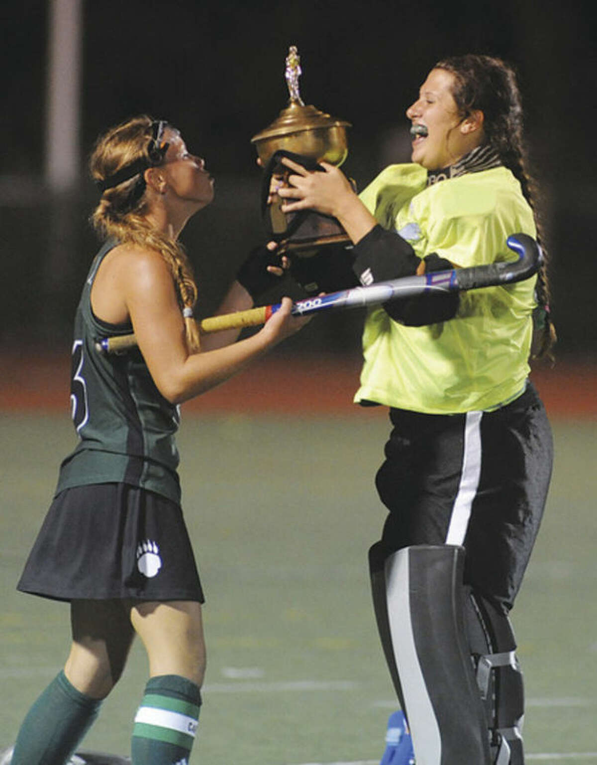 Hour photo/John Nash Norwalk's Greta McConnell, left, and Shannon O'Malley share a moment with the trophy that goes to the winner of their team's annual game with crosstown rival Brien McMahon. Norwalk won the game, 3-1, to keep the trophy for a third straight season.