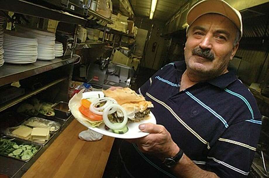"Silver Diner diner owner Andy Savvidis with a plate of ""spanakopit"" spinach pie. The diner is celebrating it''s 30th year. hour photo/matthew vinci"