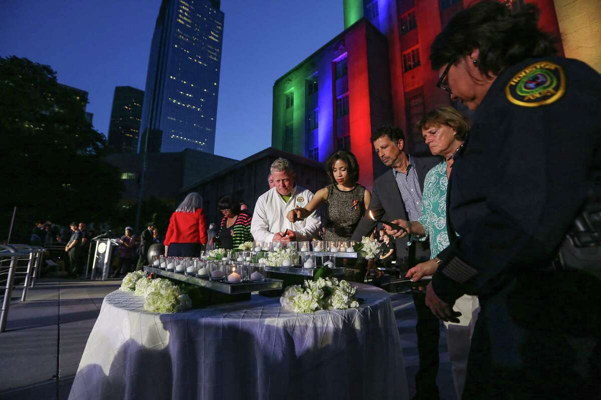 Officials at a Houston vigil on Wednesday lights candles in honor of the victims of the Orlando shooting.