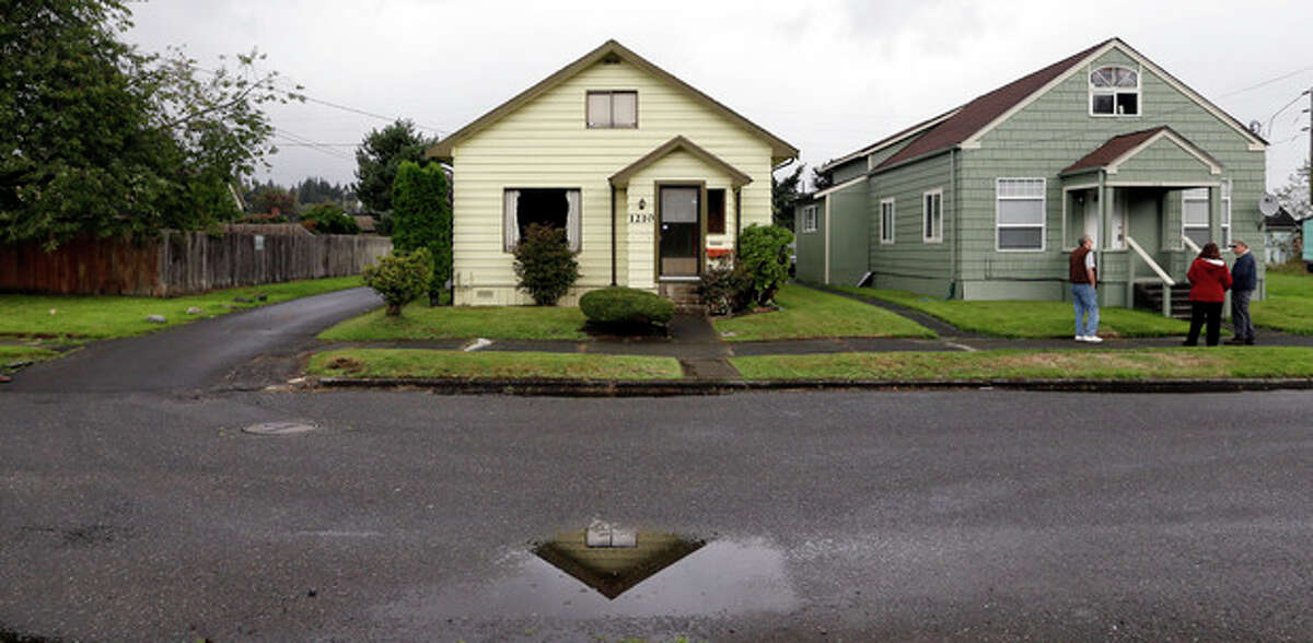 This Monday, Sept. 23, 2013 photo shows the childhood home of Kurt Cobain, the late frontman of Nirvana, left, along an alley in Aberdeen, Wash. Cobain's mother is putting the tired, 1.5-story Aberdeen bungalow on the market this week, the same month as the 20th anniversary of Nirvana's final studio album. The home, last assessed at less than $67,000, is being listed for $500,000, but the family would also be happy entering into a partnership with anyone who wants to turn it into a museum. (AP Photo/Elaine Thompson)