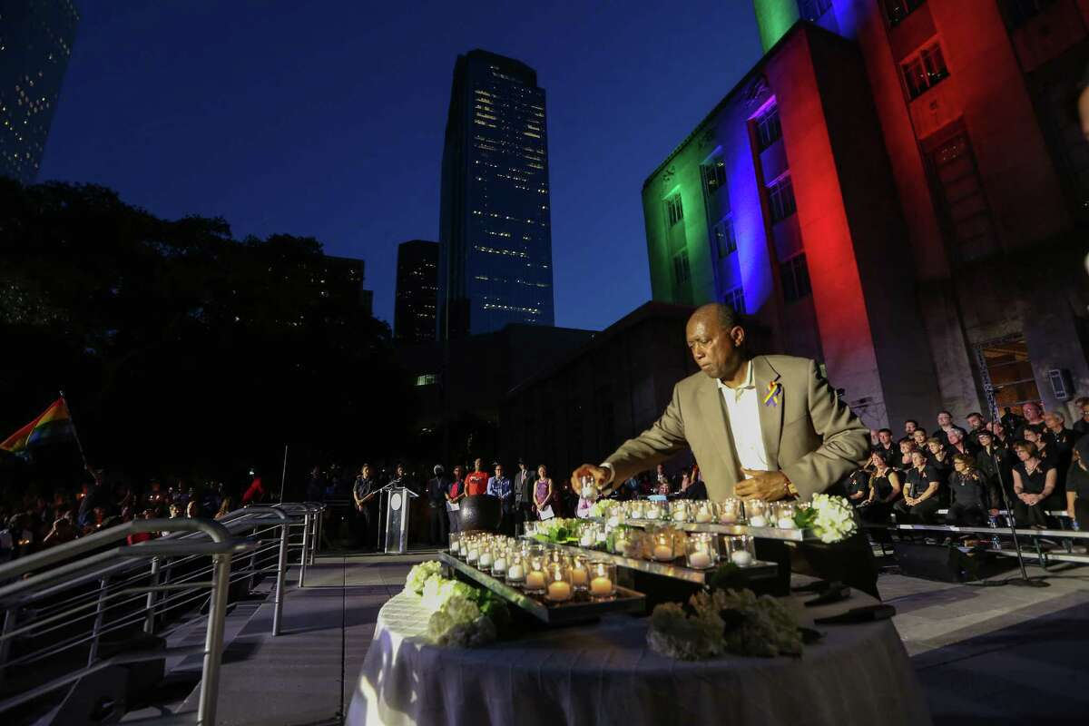 Mayor Sylvester Turner lights the last candle at the vigil on Wednesday.