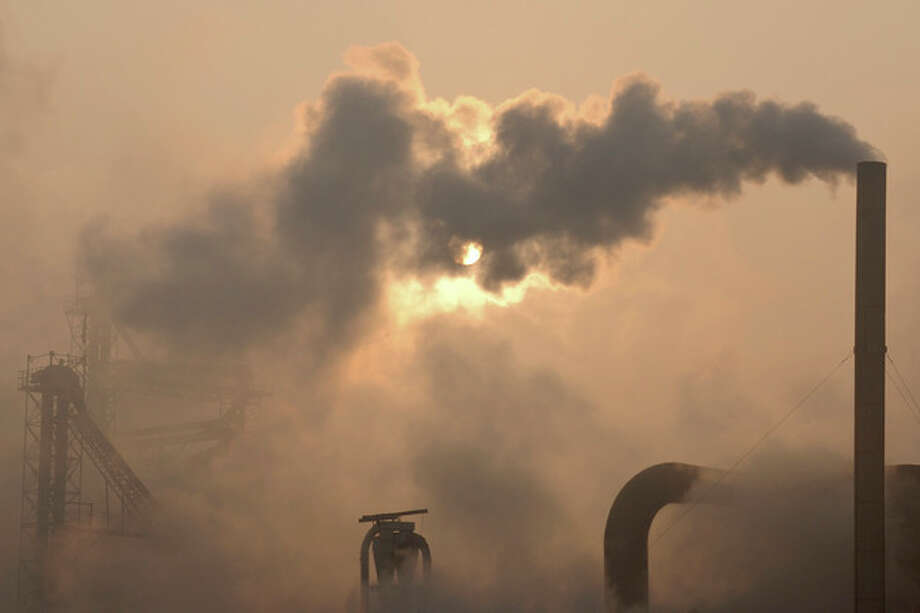 "FILE - Smoke pours from a chimney at a cement plant in Binzhou city, in eastern China's Shandong province, Thursday, Jan. 17, 2013. Scientists from around the world have gathered in Stockholm in September 2013 for a meeting of a U.N. panel on climate change and will probably issue a report saying it is ""extremely likely"" - which they define in footnotes as 95 percent certain - that humans are mostly to blame for temperatures that have climbed since 1951. (AP Photo) / CHINATOPIX"
