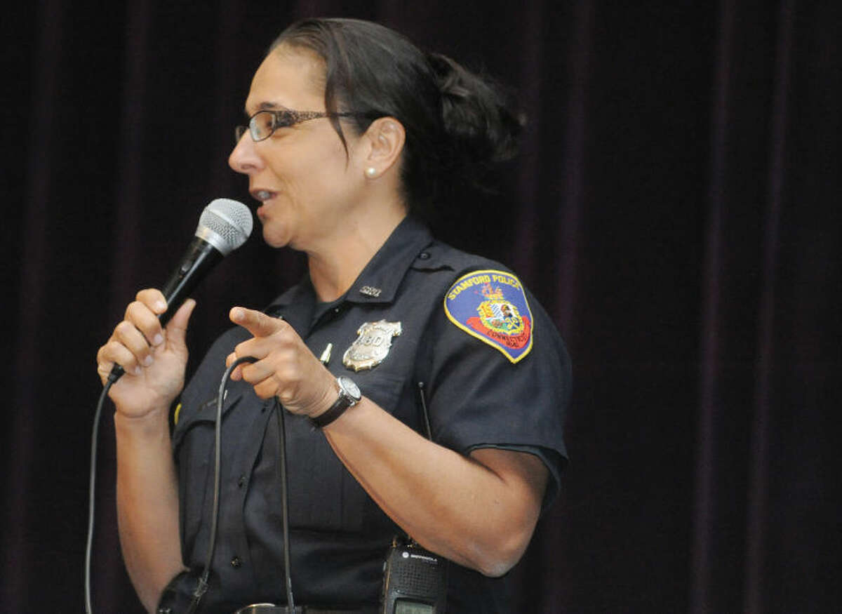 Stamford police officer Adriana Molina speaks Tuesday to bilingual students at Westhill High School on a presentation by several community leaders who have overcome similar issues.