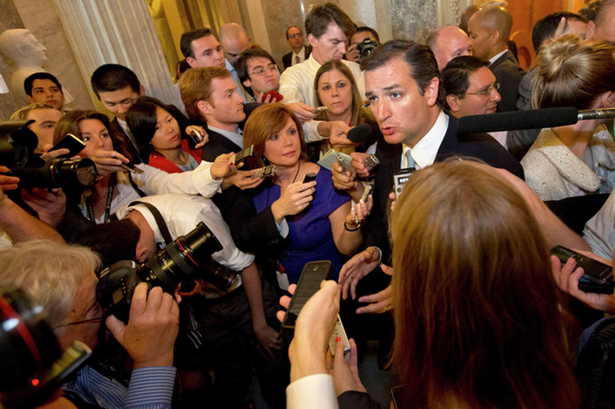 Sen. Ted Cruz, R-Texas, right, speaks to the media after leaving a marathon speech on the Senate floor on Capitol Hill in Washington, Wednesday, Sept. 25, 2013. Cruz ended the marathon Senate speech opposing President Barack Obama's health care law after talking for 21 hours, 19 minutes. (AP Photo/Jacquelyn Martin)