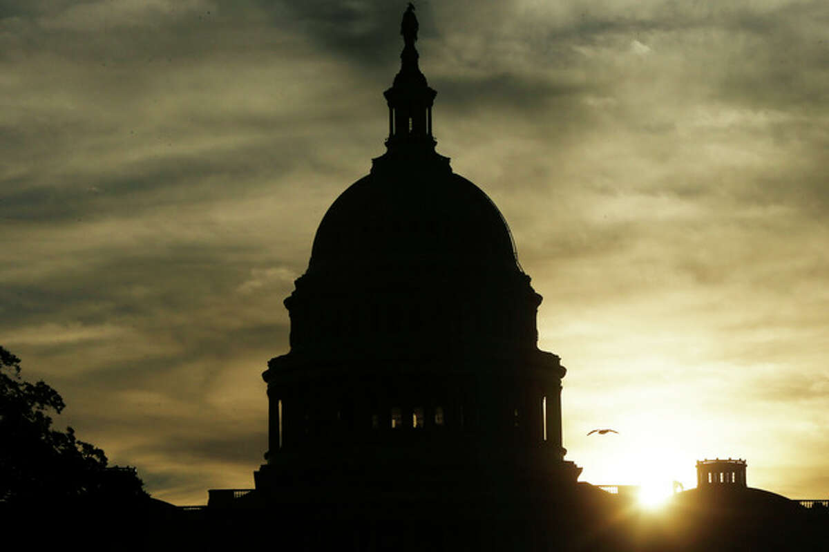 The sun rises over the U.S. Capitol as Sen. Ted Cruz, R-Texas, continues his filibuster on the Senate floor in Washington, Tuesday, Sept. 24, 2013. Cruz says he will speak until he's no longer able to stand in opposition to President Barack Obama's health care law. Cruz began a lengthy speech urging his colleagues to oppose moving ahead on a bill he supports. The measure would prevent a government shutdown and defund Obamacare. (AP Photo/Charles Dharapak)