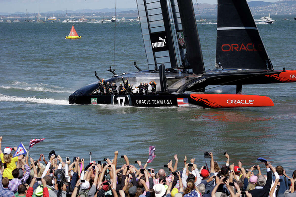 The crew on Oracle Team USA celebrates after winning the 19th race against Emirates Team New Zealand to win the America's Cup sailing event, as fans wave in the foreground Wednesday, Sept. 25, 2013, in San Francisco. (AP Photo/Marcio Jose Sanchez)