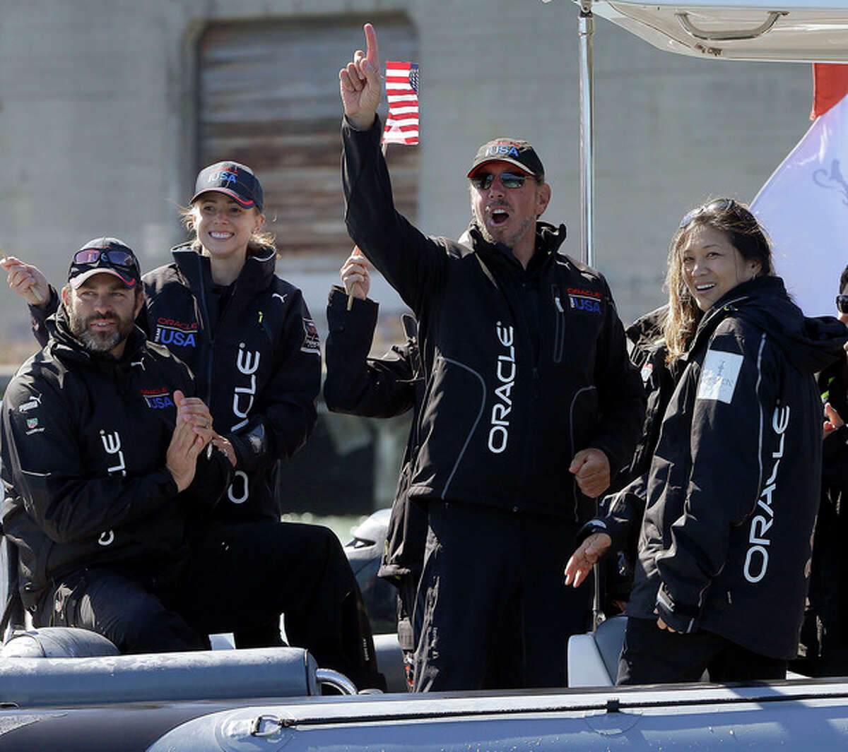 Oracle CEO Larry Ellison, center right, gestures after Oracle Team USA won the 18th race of the America's Cup sailing event against Emirates Team New Zealand, Tuesday, Sept. 24, 2013, in San Francisco. Oracle Team USA won races 17 and 18 to pull even with Emirates Team New Zealand. (AP Photo/Ben Margot)