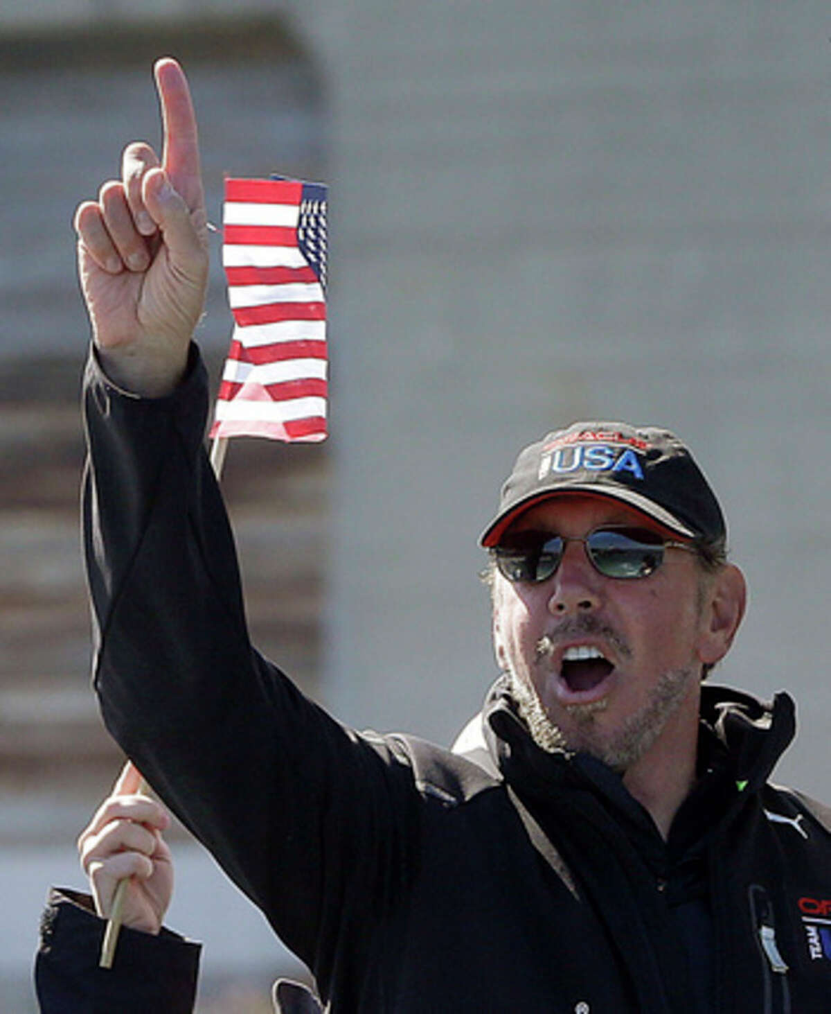 Oracle CEO Larry Ellison, gestures after Oracle Team USA won the 18th race of the America's Cup sailing event against Emirates Team New Zealand Tuesday, Sept. 24, 2013, in San Francisco. Oracle Team USA won races 17 and 18 to pull even with Emirates Team New Zealand. (AP Photo/Ben Margot)