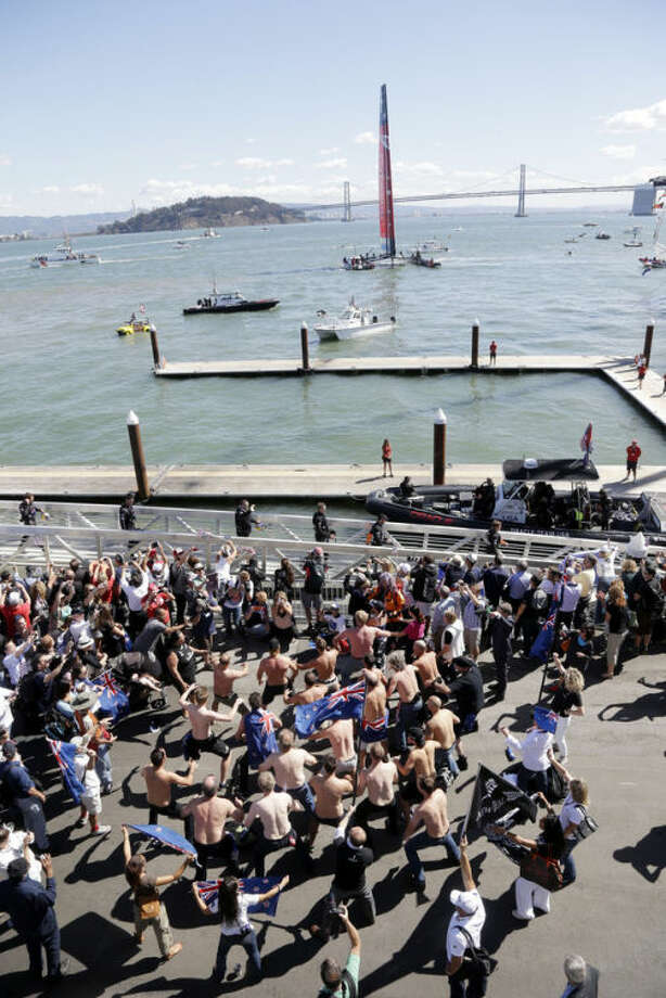 Members of Oracle Team USA board on a dock in preparation for the 19th race of the America's Cup sailing event against Emirates Team New Zealand, boat seen in the background, on Wednesday, Sept. 25, 2013, in San Francisco.(AP Photo/Marcio Jose Sanchez)