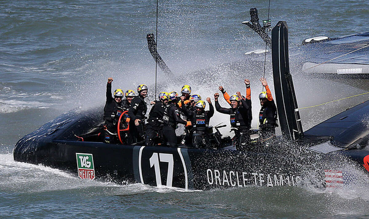 The crew on Oracle Team USA celebrates after winning the 19th race against Emirates Team New Zealand to win the America's Cup sailing event, Wednesday, Sept. 25, 2013, in San Francisco. (AP Photo/Marcio Jose Sanchez)