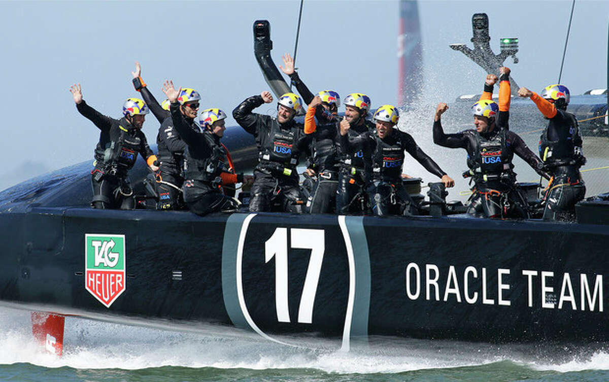 Crew memebers on Oracle Team USA celebrate after crossing the finish line to win the 18th race of the America's Cup sailing event against Emirates Team New Zealand, Tuesday, Sept. 24, 2013, in San Francisco. Oracle Team USA won races 17 adn 18 to pull even with Emirates Team New Zealand. (AP Photo/Ben Margot)