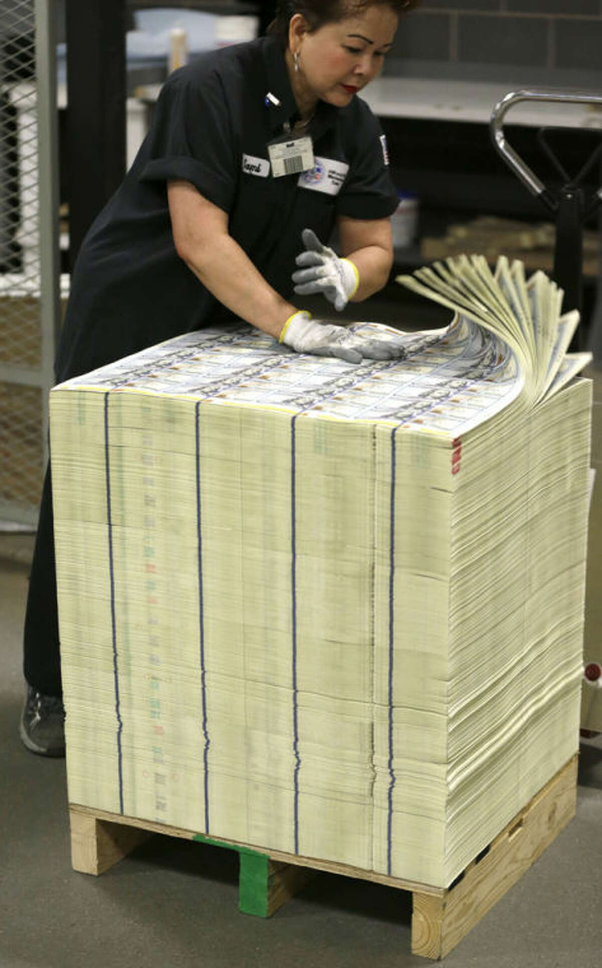 A stack of uncut sheets of $100 bills are inspected before being moved during the printing process at the Bureau of Engraving and Printing Western Currency Facility in Fort Worth, Texas, Tuesday, Sept. 24, 2013. The federal printing facility is making the new-look colorful bills that include new security features in advance of the Oct. 8 circulation date. (AP Photo/LM Otero)