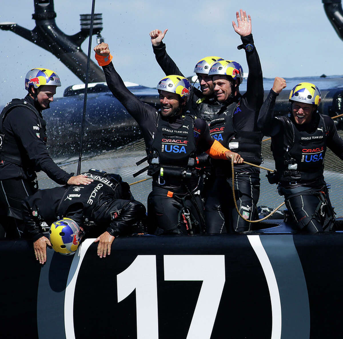 Oracle Team USA crew celebrate as grinder Simeon Tienpont, second fromleft, leans over the side to kiss the boat after winning the 19th race against Emirates Team New Zealand to win the America's Cup sailing event Wednesday, Sept. 25, 2013, in San Francisco. (AP Photo/Ben Margot)