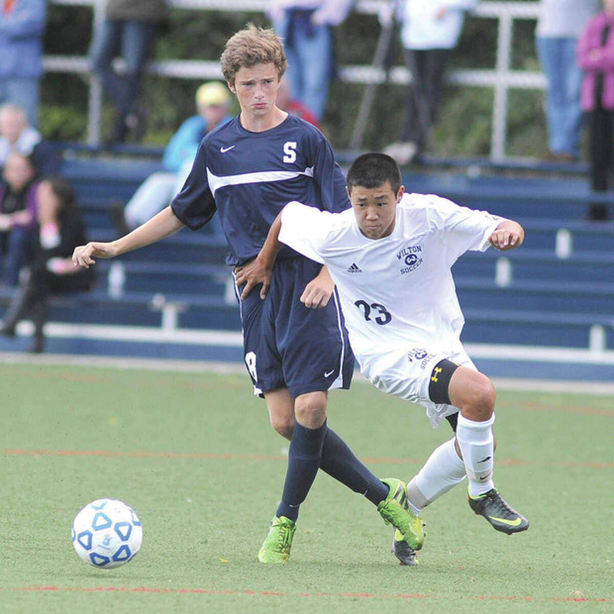 Hour photo/John Nash Wilton's Michael Lynch, right, gets around Staples' Michael Reid to track down a ball during the second half of Wednesday's FCIAC boys soccer game at Lilly Field in Wilton.