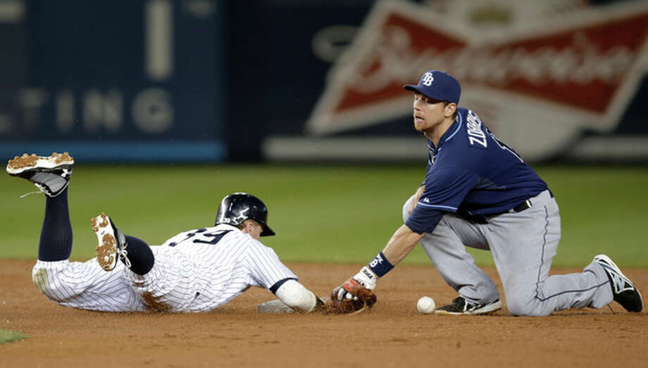 New York Yankees' Mark Reynolds (39) is safe at second on a second-inning sacrifice fly as Tampa Bay Rays second baseman Ben Zobrist loses the ball in a baseball game Wednesday, Sept. 25, 2013, in New York. (AP Photo/Kathy Willens) / AP