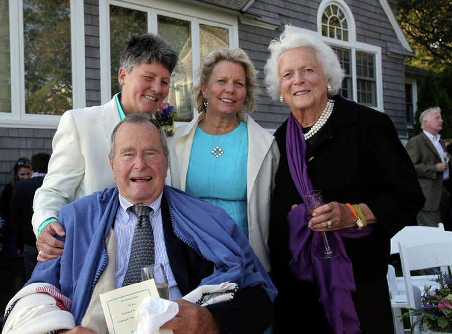 In this Sept. 21, 2013 photo, former President George H.W. Bush, front left, former first lady Barbara Bush, right, pose for photos after wedding of longtime friends Helen Thorgalsen, center, and Bonnie Clement, in Kennebunkport, Maine. Bush was an official witness at the same-sex wedding, his spokesman said Wednesday, Sept. 25, 2013. (AP Photo/Susan Biddle) / AP