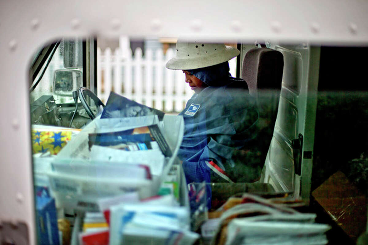 FILE - In this Thursday, Feb. 7, 2013, file photo, U.S. Postal Service letter carrier, Jamesa Euler, delivers mail, in Atlanta. The financially struggling Postal Service said Wednesday, Sept. 25, 2013, it is seeking a 3-cent increase in the cost of mailing a letter, bringing the price of a first-class stamp to 49 cents. (AP Photo/David Goldman, File)