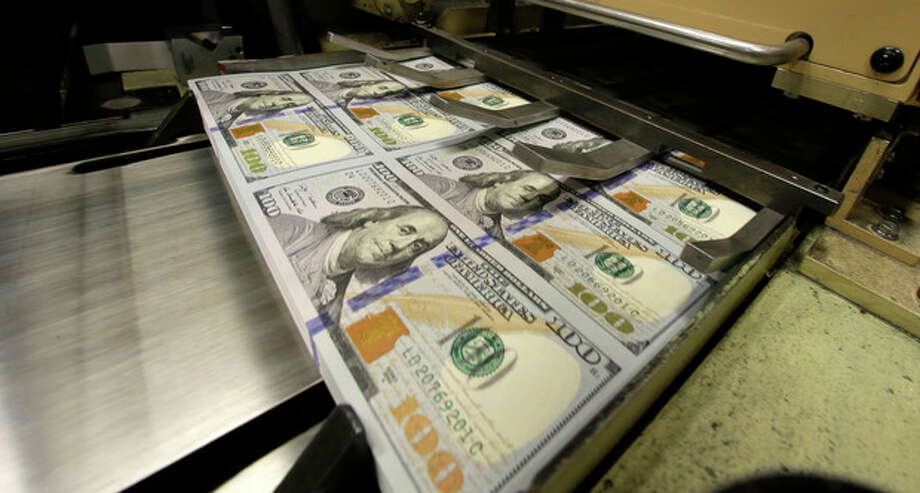 Uncut $100 bills run through cutting machine at the Bureau of Engraving and Printing Western Currency Facility in Fort Worth, Texas, Tuesday, Sept. 24, 2013. The federal printing facility is making the new-look colorful bills that include new security features in advance of the Oct. 8 circulation date. (AP Photo/LM Otero) / AP
