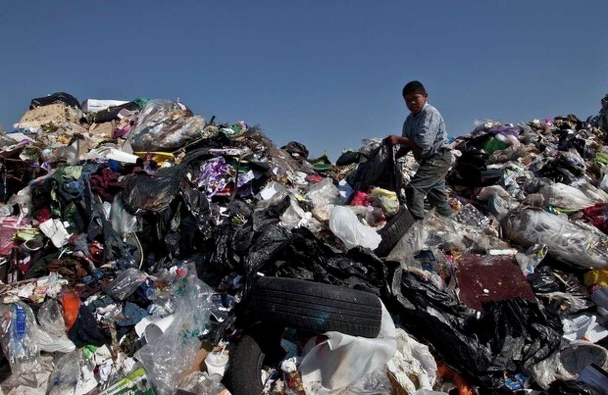 FILE - In this Dec. 19, 2011 file photo, a boy selects garbage to recycle at the landfill Bordo Poniente on the outskirts of Mexico City. This dump was closed at the end of 2011 but the compost site within the dump continues to operate. Mexico City Mayor Miguel Mancera announced plans in September 2013 to control the foul odors that waft from the city?'s only compost plant at this landfill near the airport and to more aggressively recycle trash citywide. (AP Photo/Christian Palma, File)