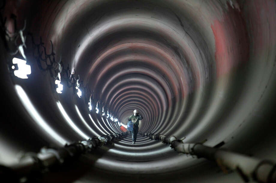 FILE - In this March 18, 2009 file photo, a worker walks inside an underground deep drainage tunnel system that handles rainwater and sewage in Mexico City. Experts agree the main source of the capital's odor problems is from an overwhelmed sewage system. (AP Photo/Dario Lopez-Mills, File) / AP
