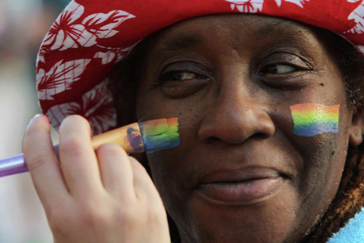 Joy Matthews has a rainbow flag painted on her face during a candlelight vigil for Orlando victims at City Hall.