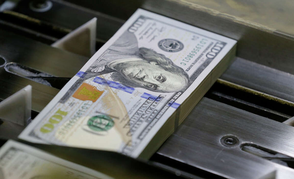 A just cut stack of $100 bills rolls down the line at the Bureau of Engraving and Printing Western Currency Facility in Fort Worth, Texas, Tuesday, Sept. 24, 2013. The federal printing facility is making the new-look colorful bills that include new security features in advance of the Oct. 8 circulation date. (AP Photo/LM Otero)