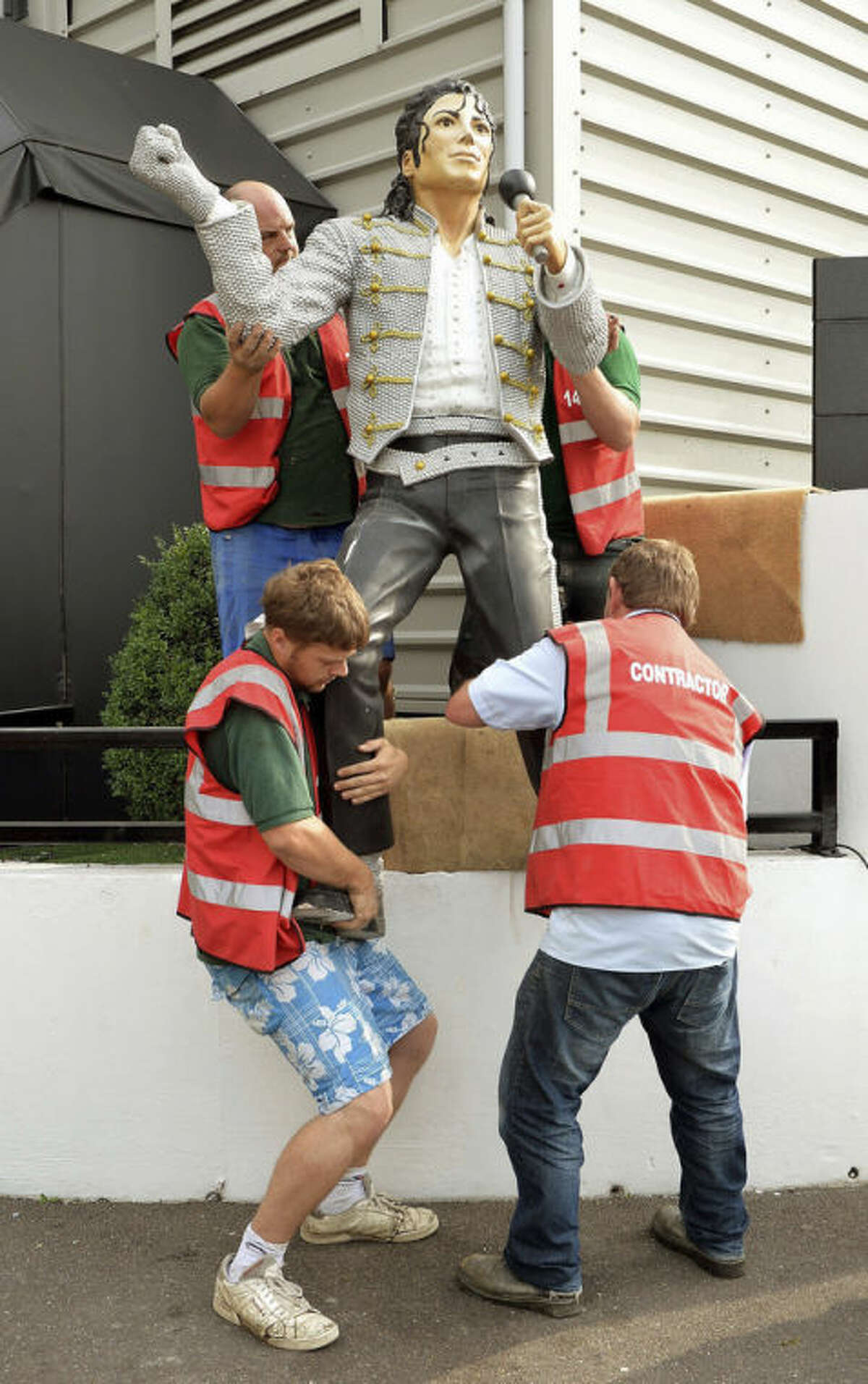 A group of stonemasons remove the statue of US performer Michael Jackson, that was erected by previous owner Mohammed al Fayed, on the north west corner of Fulham Football Club, in London, Wednesday Sept. 25, 2013. The controversial Michael Jackson statue which has stood outside Fulham's Craven Cottage ground for over two years was removed on Wednesday. Al Fayed sold the west London club to Shahid Khan in July and, after consulting with supporters, the American businessman decided to pull the 7ft 6in statue down. (AP Photo/PA, John Stillwell) UNITED KINGDOM OUT NO SALES NO ARCHIVE