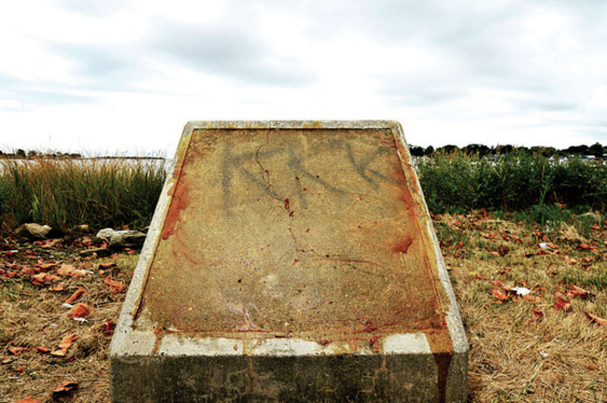 Hour photo / Erik Trautmann Someone spray painted the letters, k-k-k on a concrete monument at Veteran's Memorial Park in Norwalk recently.
